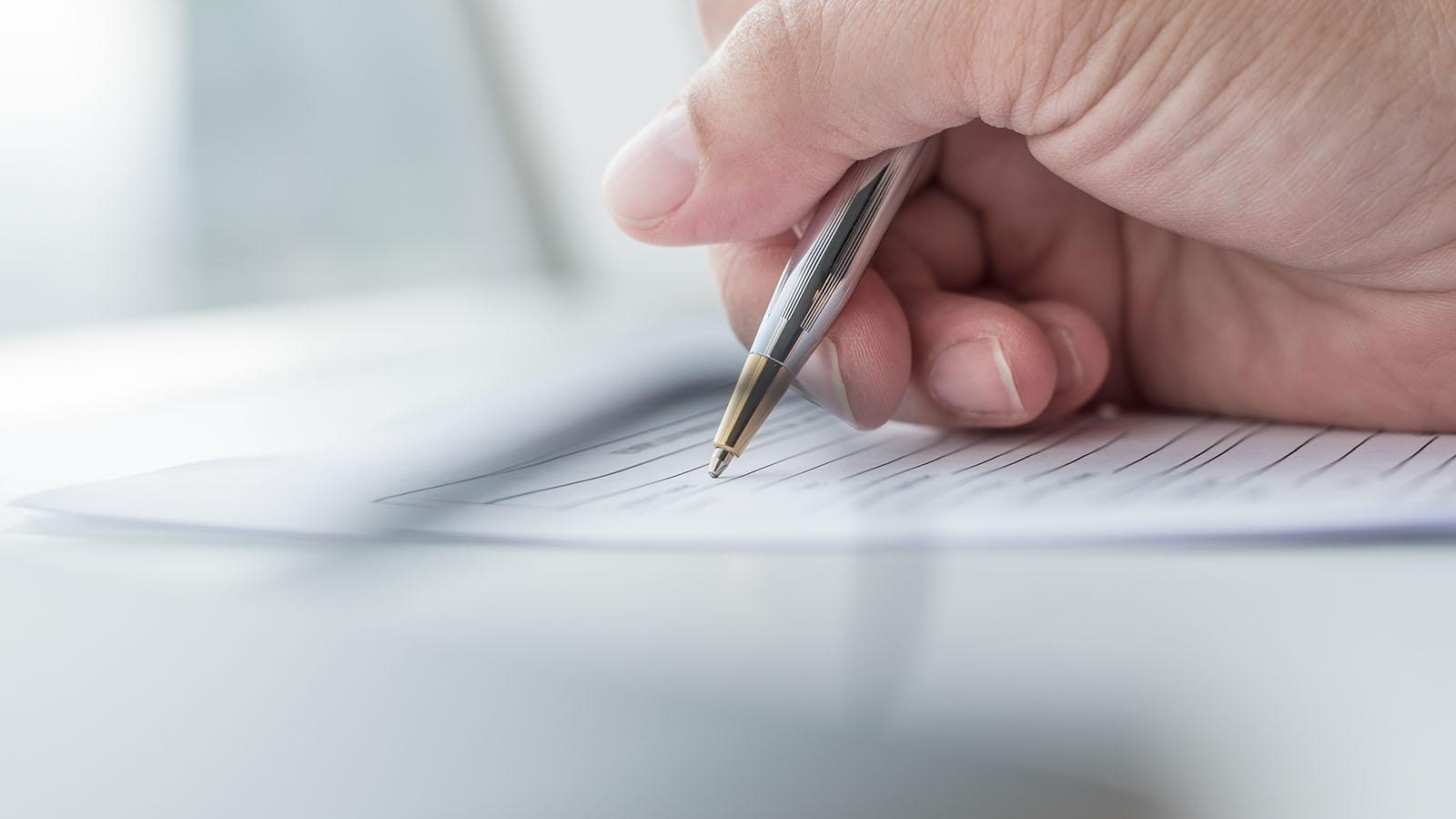 Main d'une personne écrivant sur une feuille de papier